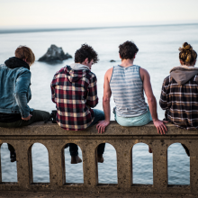 Four Young People Sitting on Ledge